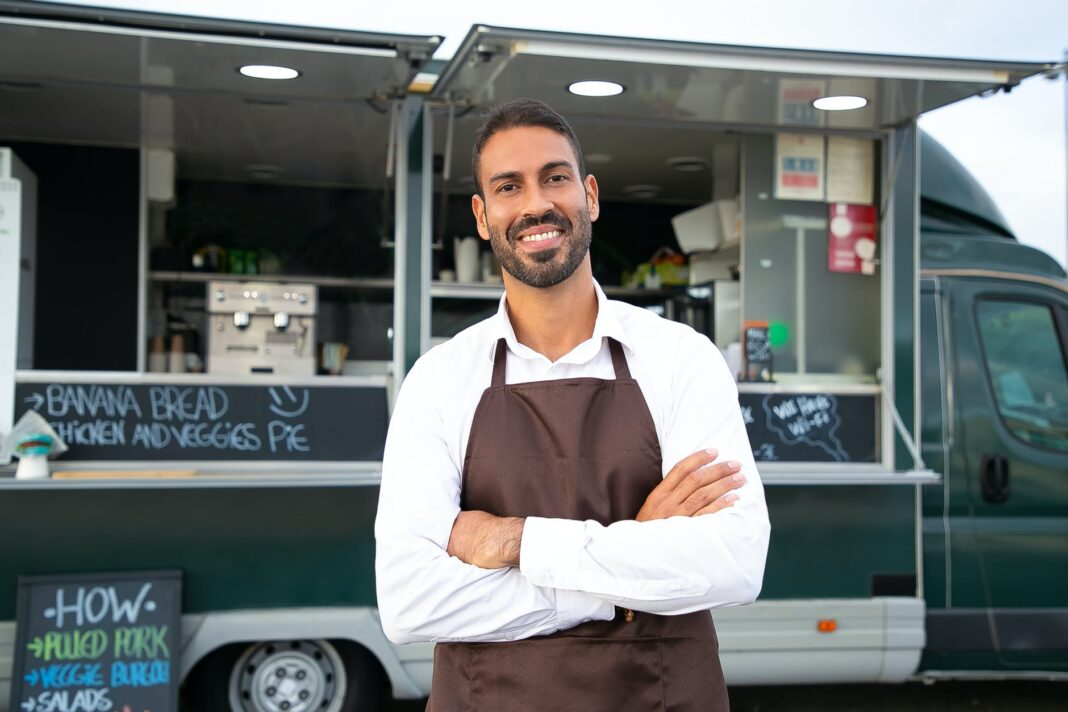 cheerful ethnic male food truck waiter standing with crossed arms